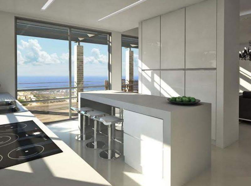 מטבח מודרני בחיפוי זכוכית לבנה עם נוף לים